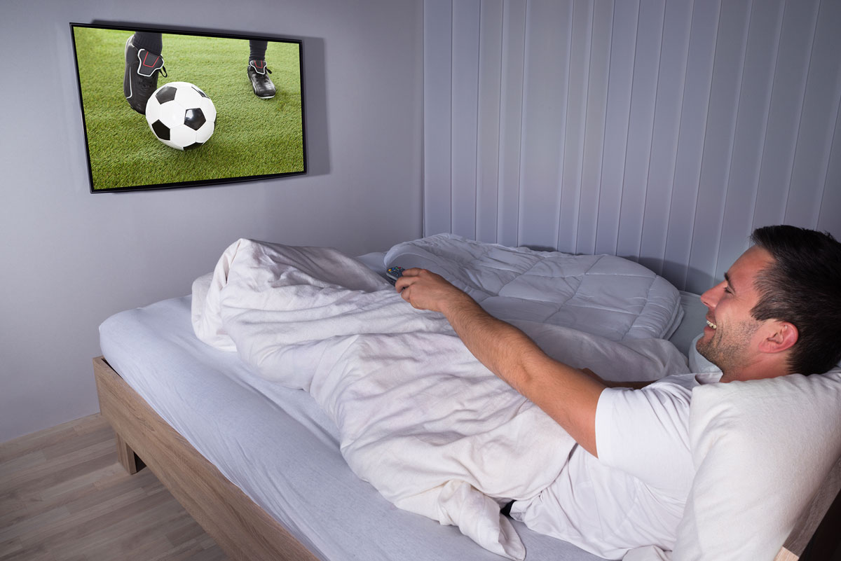 A man watching a football game in bed