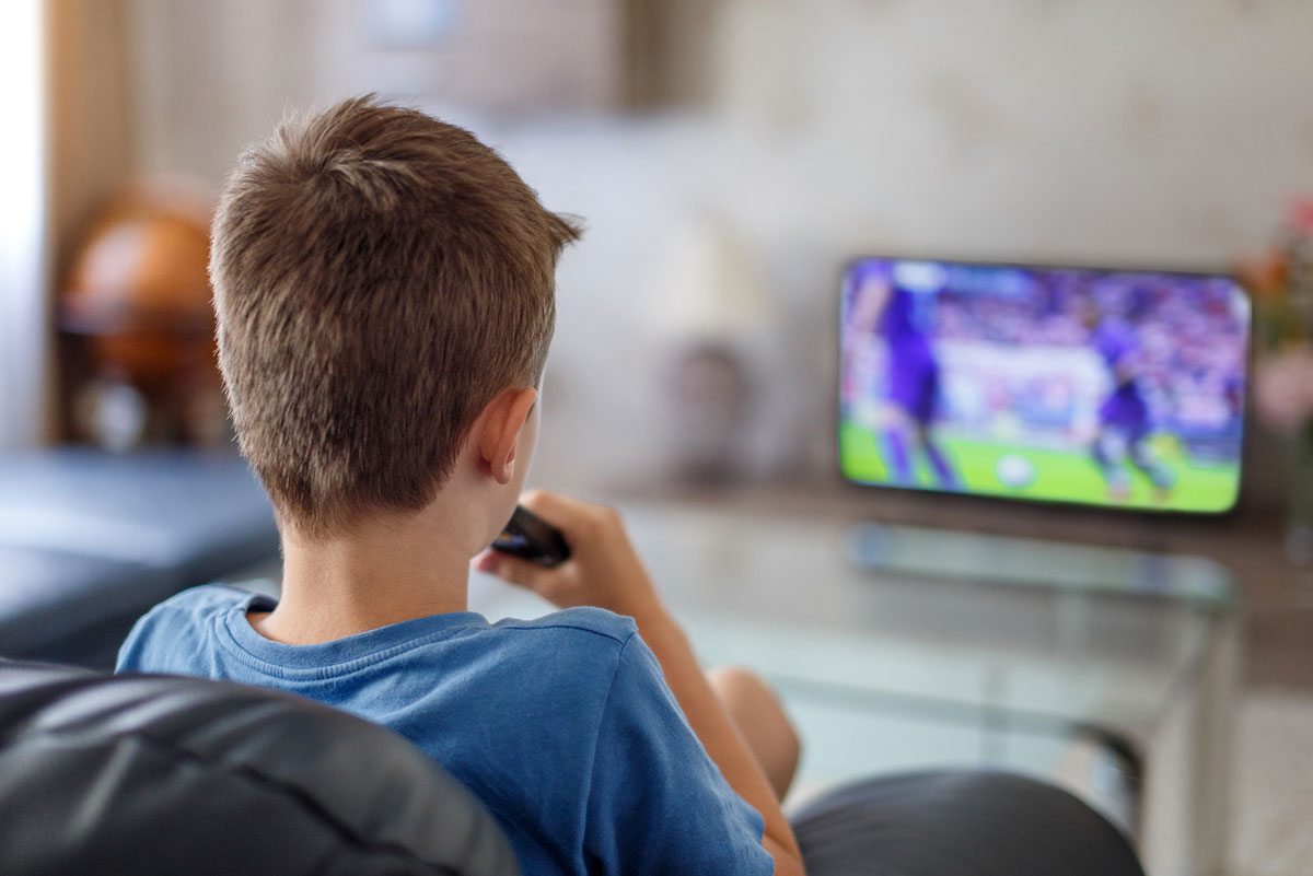 A child watching sport in his bedroom