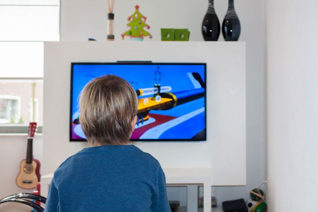 A child playing computer games on a TV mounted to a wall